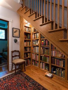 This is the best bookshelf idea! Turn the space under the stairs into a cozy home library by using floor-to-ceiling built-in bookshelves -- and don't forget the lighting! #basementremodel