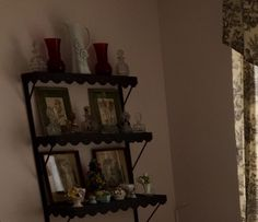 Shelf painted in flat black auto undercoat displays perfume bottle and porcelain flower collection.