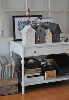 Winter decoration - tea light houses and blankets in a wooden crate