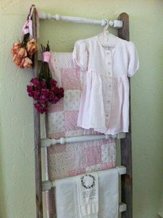 old ladder holds quilts, linens, little girl dress and roses