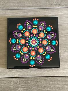This versatile coaster is not only designed to protect your furniture but also adds some beautiful artistic spice to your home. This black ceramic coaster is 4 x 4 inches, painted with enamel paint and can be Dot Painting Tools, Rock Painting Patterns, Dot Art Painting, Rock Painting Designs, Mandala Canvas, Mandala Artwork, Mandala Painting, Mandala Painted Rocks, Mandala Rocks