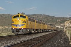 """Union Pacific E9A 949 leads the Westbound """"City of Los Angeles"""" excursion train as it performs a photo run by for passengers. We are at a beautiful area called Meadow Valley Wash near the Utah-Nevada border. Unfortunately we departed Milford,Utah without UP Challenger 3985 and traveled west behind the ABA set of excursion E units to Las Vegas,NV. UP 3985 rejoined us at Las Vegas the next morning and we continued on to Ontario,CA. Photo taken by Thomas Kidd @ May 13,1994, 20xx."""