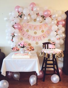 A pink and gold first birthday party with florals, gold polka dots, party macarons, donuts smash, birthday cake and balloon arch.