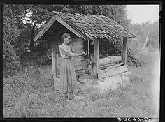 Miss Nettie Lloyd, pellagra victim, by their old well house. Orange County, North Carolina. September 1939. Photo by Marion Post Wolcott.