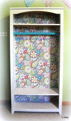 Kid closet from cheap bookcase / wrapping paper on back panel, white spray paint and a blue dowel