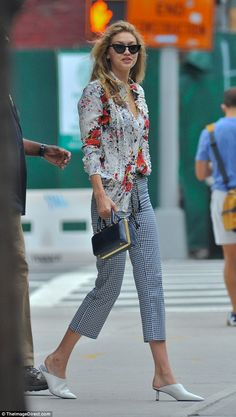 Edgy: Gigi Hadid rocked a floral print top with gingham pants and kitten heels in NYC Satu...