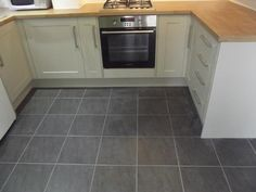 This dark grey floor enhances the subtler shade of the cabinets.   http://www.ppmsltd.co.uk