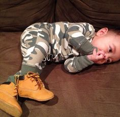 Adorable baby boy in camo bodysuit and baby Timberlands