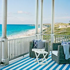 A bright blue-and-white striped rug brings a burst of color to this otherwise simple porch | Coastalliving.com