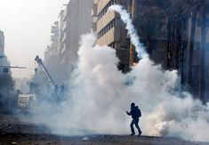 A protester returns a tear gas canister to the riot police in Cairo on Nov. 25.