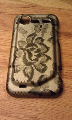 """""""my DIY cell phone case.  I followed the instructions on my pin in my DIY Projects board.  I used a black cell phone case and covered it with lace.  I used silver spray paint over the lace and then polyurethane spray paint to finish."""""""