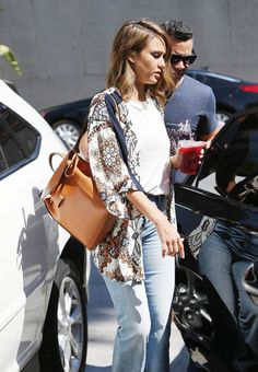 Jessica Alba wears a printed tunic and leather backpack over a T-shirt and jeans.