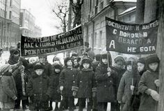 "Left banner: ""Parents, do not confuse us, do not do Christmas and the Christmas tree"" Right banner: ""to raise children with the help of the teacher, not God,"" Moscow, Bauman district."