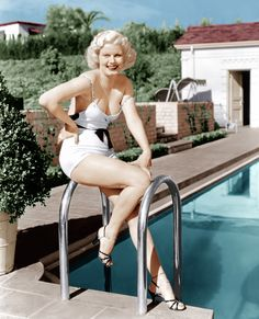 JEAN HARLOW Publicity Still, circa 1935  The It Girl of the 1930s, Jean Harlow was known for her platinum hair and bombshell figure. She showed off her curvy body in this iconic publicity still where she posed poolside in fabulous heels and scandalously slipping straps.