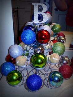 """Cupcake stand + inexpensive ornaments + initial tag/ornament = fun, festive Christmas """"tree"""" decoration. We didn't have enough ornaments, so I used corks to fill the empty spaces."""