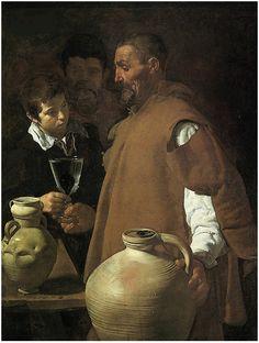 """""""El aguador de Sevilla"""" Velázquez. De su etapa sevillana (1619-1622). Aparecen en primer plano, un aguador y un niño, y al fondo un hombre bebiendo en un jarro, por lo que podría representar las tres edades del hombre. Destaca por su realismo, como demuestra en la mancha de agua del cántaro de primer plano; la copa de cristal, con un higo para dar sabor al agua, o los golpes del jarro de la izquierda. También en las figuras humanas, interesándose por los efectos de luz y sombra."""