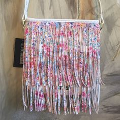 Steve Madden Cross-Body Brand new floral fringe purse that is perfect for spring and summer!  This bag has magnetic snap closure and on the inside it has one zip pocket and two slip pockets. Made of polyester and PVC. About 9.5 inches tall and 9 inches across. Feel free to ask any questions and offers are welcome :) Steve Madden Bags Crossbody Bags