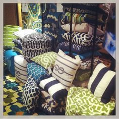 Surya outdoor pillows and poufs on display in bright greens and blues at Saywell Interiors. Also using our Pillow Tower to display up to 20 different patterns. | Suryasocial on Instagram