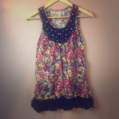 Flowery summer shirt Multicolored with flowers pattern. Black ruffles on the bottom and gold bedazzled neckline. SHIRT SAYS LARGE BUT IT FITS SMALL BETTER. Tops Tank Tops