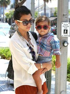 kourtney kardashian & mason. white blouse, rust shorts, necklace, black bag, bun, wayfarers.