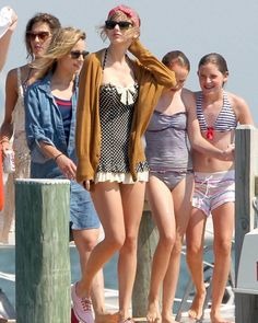 Taylor Swift's Polka dot frilly one-piece swimsuit with red stripey shoes and polka dot headband.  Outfit details: http://wwtaylorw.com/1059/