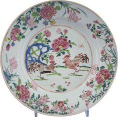 Assiette à décor de deux coqs affrontés en porcelaine de Chine de la Compagnie des Indes d'époque Yongzheng La scène centrale, entourée d'un double cerclage en guise de médaillon, représente deux coqs affrontés s'apprêtant à combattre à coté d'un rocher percé bleu turquoise duquel émerge des pivoines en fleurs.