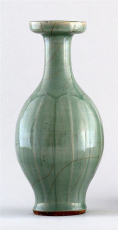 """LONGQUAN CELADON VASE Ming Dynasty  With incised leaf design, elongated neck, and flared mouth. Height 10 1/4"""" (25.5 cm)."""
