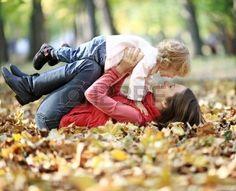 Happy family having fun in autumn park Stock Photo