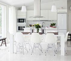Eamesin DSR-tuolit sopivat hyvin suureen valkoiseen pöytään, joka ostettiin Askosta jo vuotta ennen kuin mökki oli valmis. Pöydän yläpuolella olevat pelkistetyt riippuvalaisimet löytyivät Ikeasta. Topi-Keittiöiden keittiökalusteet kuuluivat talopakettiin, oviksi valittiin mattavalkoiset tasapainottamaan kiiltävää lattiaa. Laatat ovat 40 x 40 -senttiset marmorinvalkoiset. Tarjoiluastiat ja ruskeat penkit ovat huonekaluhalleista Kiinasta. Pöytätabletit ovat Pentikin.
