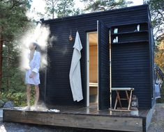 sauna in the yard with black woods exterior along with fantastic shower outside and simply shelving also small stool