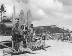 This classic photograph taken on Waikiki Beach during WWII features Duke Kahanamoku and others displaying trophies while apparently promoting an upcoming surfing or paddling competition.