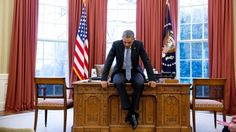 Barack Obama sits on his desk in the Oval Office, deep in thought