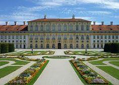Het paleis van Illea heeft een lange oprijlaan met op het einde een ronde fontein. Het heeft lichtgeel gestuukte muren die heel hoog zijn.  Pagina 78