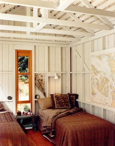 summer cabin feel - white washed walls, richly colored bedding & a map on the wall