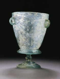 A LATE ROMAN FOOTED BEAKER OR LAMP circa 5th-7th century a.d. Transparent bluish-green in color, the bucket-shaped body with a pinched down-turned flange at the base, a conical foot on a double knobbed stem, and three applied loop handles below the rim 76 in. (17.9 cm) high