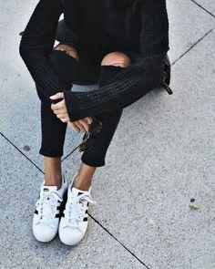 Black ripped jeans, black sweater, + Adidas Superstars.