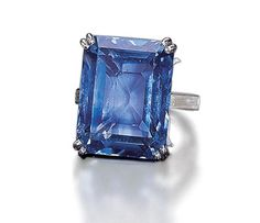 A SAPPHIRE RING, BY BOUCHERON   Set with a rectangular-cut sapphire weighing 52.09 carats to the baguette-cut diamond shoulders and plain hoop, with French assay marks for platinum  Signed Boucheron, Paris