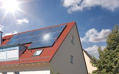The sun shines brightly on solar panels atop a roof.
