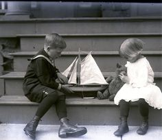 Girl with her teddy bear & a boy with his toy sailing boat, circ. 1900