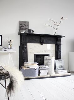Scandanavian inspired living room with black fireplace and modern metal chair with lamb throw