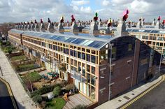 Perhaps most well known 'zero-carbon community'.  'BedZed' 2002.  Architect: Bill Dunster.  82 affordable homes, mix of flats, maisonettes & houses, & ~2500m2 of workspace/ office, brownfield site, biomass CHP (5-15% surplus energy pa), onsite sewage treatment & rainwater recycling system, easy to read energy meters in kitchens, well insulated envelope, use of passive solar gain w. stack ventilation.