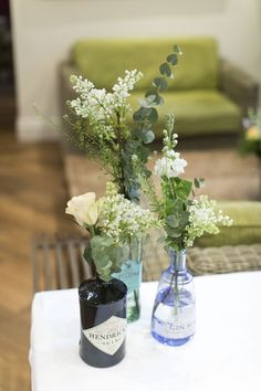 Gin bottles as vases // eucalyptus // roses // Mitton Hall wedding