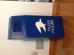 """I made this mailbox for my 3-year old who loves playing """"post office"""" at her preschool. I used a cardboard box for the base and then used masking tape to connect the top pieces of cardboard. I spray painted it and drew an eagle on the front and painted it. I had a round, wooden piece that I allowed my daughter to paint black and hot glued it on as a knob where she sticks her mail into the box. I cut out an opening in the back so she can retrieve the mail she sends."""