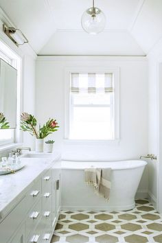 In the master bath, the all-white space is broken up with graphic floor tile by Ann Sacks.