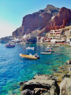 Santorini | Greece, Amoudi Beach. Crystal clear water surrounded by red cliffs, boats and blue skies.