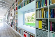 integrated bookshelf and window seat at the Long Brick House by Földes Architects. This corridor is the spine of the house and the bookshelf really brings it to life!   #furniture #architecture #design #interiordesign #books