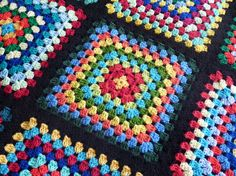 This beautiful, colourful blanket is made of nine granny squares in an assortment of colours edged and joined with black. The effect is stunning.  Lovely and snuggly this blanket measures 34 square which makes it perfect for a baby blanket, small lapghan, wheelchair knee cosy, throw for the back of a chair or an assortment of other things.    Made using good quality acrylic yarn, the blanket is machine washable and can be dried on low heat, though also air dries very quickly and easily…