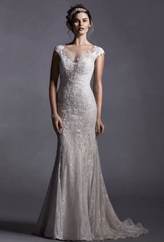 Brides: Sottero & Midgley. More details from Sottero & Midgley��Glamorous, glimmering lace appliqu�s adorn tulle in this sheath dress with illusion neckline and plunging illusion back. Complete dainty  lace cap-sleeves. Finished with covered button over zipper closure.