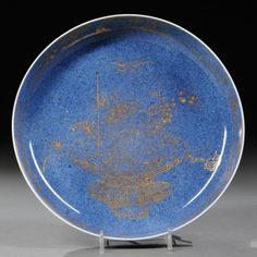 Powder Blue-glazed Porcelain Dish, China, 19th century, the interior decorated with a basket of various auspicious flowers in gilt, a prunus and pine band at the sides, dia. 8 3/4 in.
