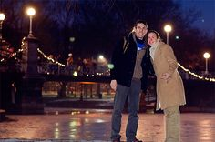 A couple standing in front of a bridge at night